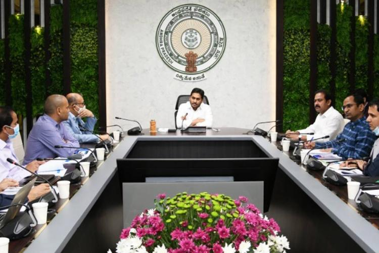 CM Jagan Mohan Reddy seated with folded arms at the head of a rectangular table with officials seated on either side of the table