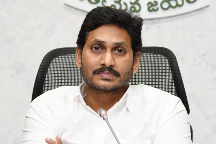 Andhra Pradesh Chief Minister Jagan Mohan Reddy wearing a white shirt sitting at his desk in front of a mic