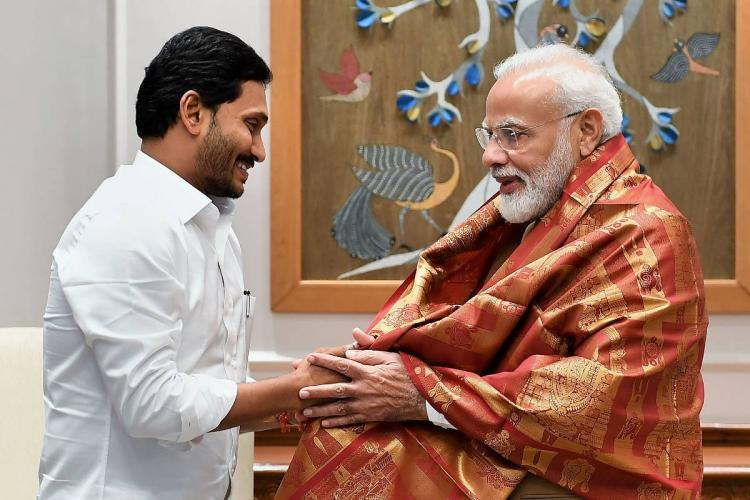 Andhra Pradesh Chief Minister Jagan Mohan Reddy wearing a white shirt, greeting Prime Minister Narendra Modi by holding his hands