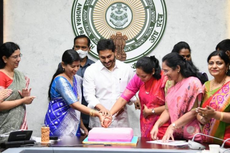 Andhra Pradesh Chief Minister Jagan Mohan Reddy wearing a white shirt, cutting a pink cake along with women officials on International Women's Day