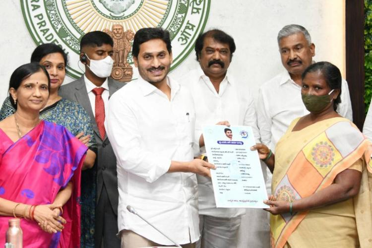 Andhra Pradesh Chief Minister Jagan handing over the YSR Bima Card to a beneficiary while surrounded by officials in his office