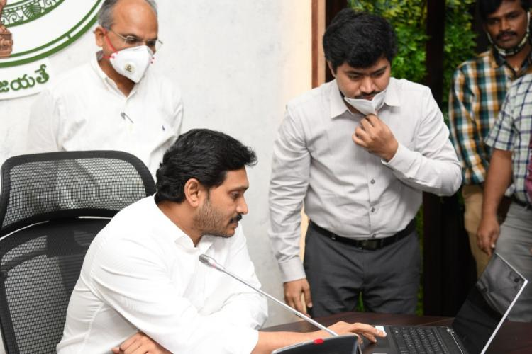 Andhra CM Jagan at the launch of Aarogyasri pilot expansion with health department officials sitting at his desk and looking into a computer
