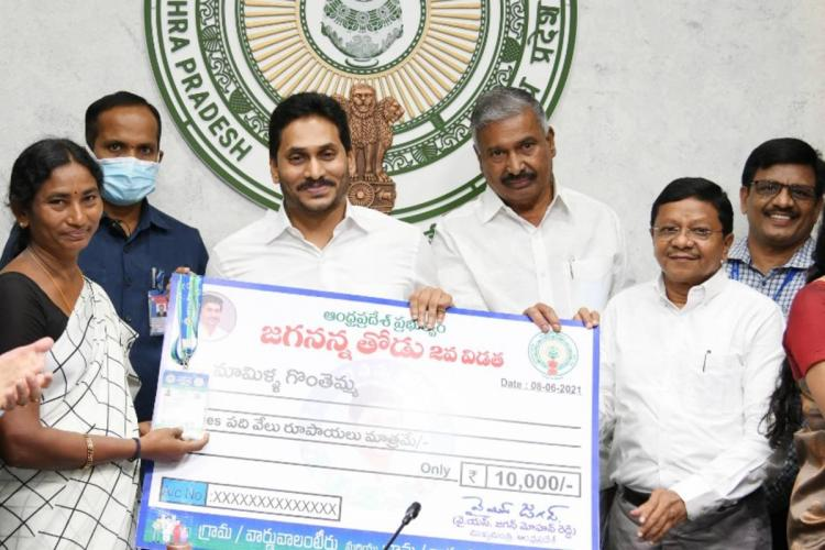 Andhra Pradesh Chief Minister Jagan Mohan Reddy handing over Jagananna Thodu scheme cheque to a beneficiary