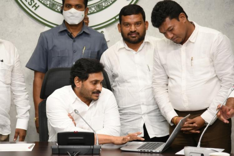 Jagan seated and using a laptop with officials standing around him