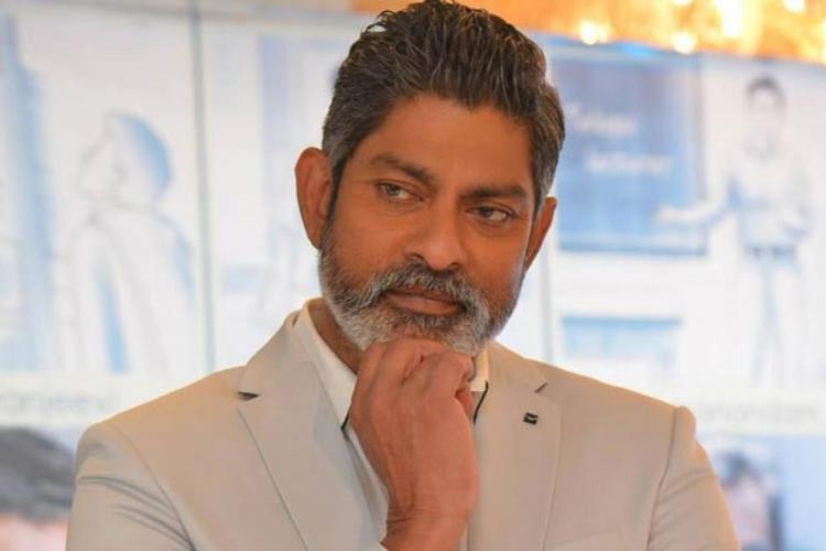 Jagapathi Babu posing in a cream-coloured jacket with one hand folded under his chin He is smiling slightly looking to his right