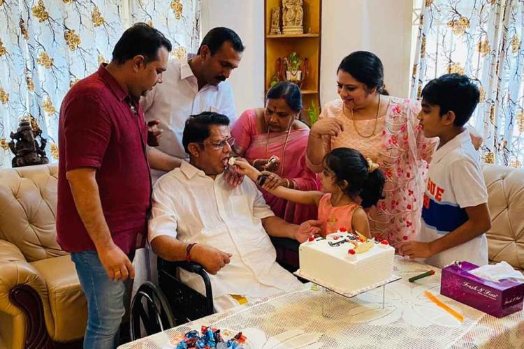 Jagathy celebrating birthday with his family members he is sitting and having cake that is given by grand daughter