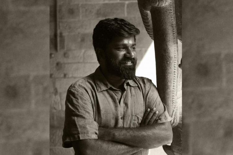 Photographer Jaisingh Nageswaran stands with his hands folded near an elephant sculpture