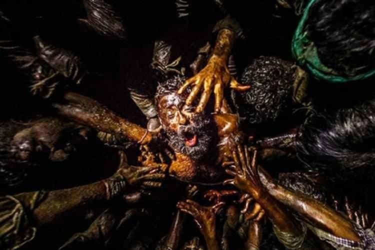 Muddy face of a man covered by many muddy hands of people standing around him