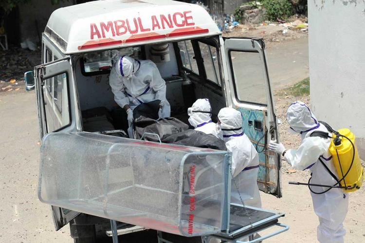 healthcare workers shift a body from an ambulance