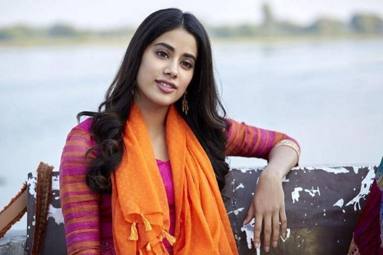 Janhvi Kapoor stands againsthe sea with her left hand resting on the side fence She is wearing a pink salwar with an orange shawl put around her neck and her straight black hair on either side