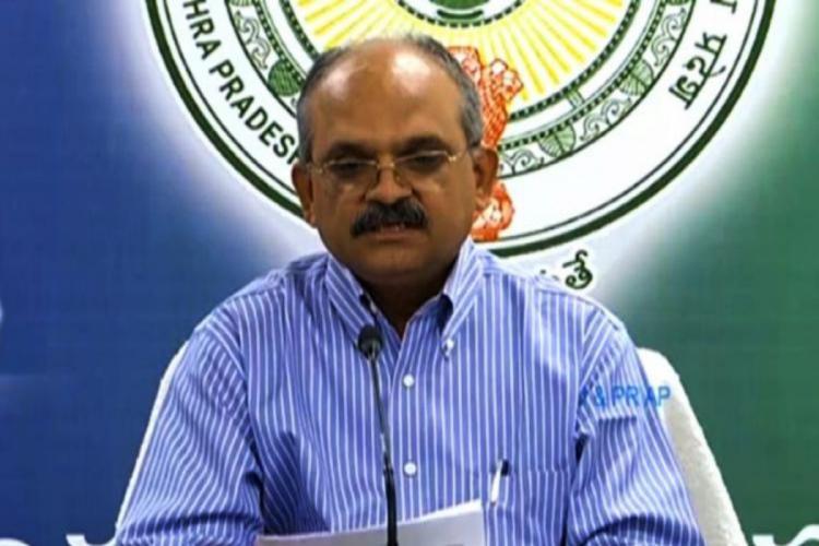 IAS officer Jawahar Reddy in a blue shirt addressing a press meet