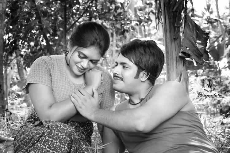 Models posing as Jayan and Seema in this black and white image The male model is wearing a vest and a black thread as a neckpiece The female model is seen in a printed blouse and sarong The man is seen holding her hand while she looks down smiling coyly