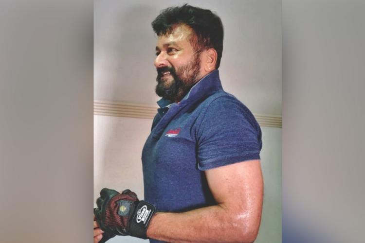 Jayaram bearded in a blue t shirt looks sideways and smiles wearing black gloves
