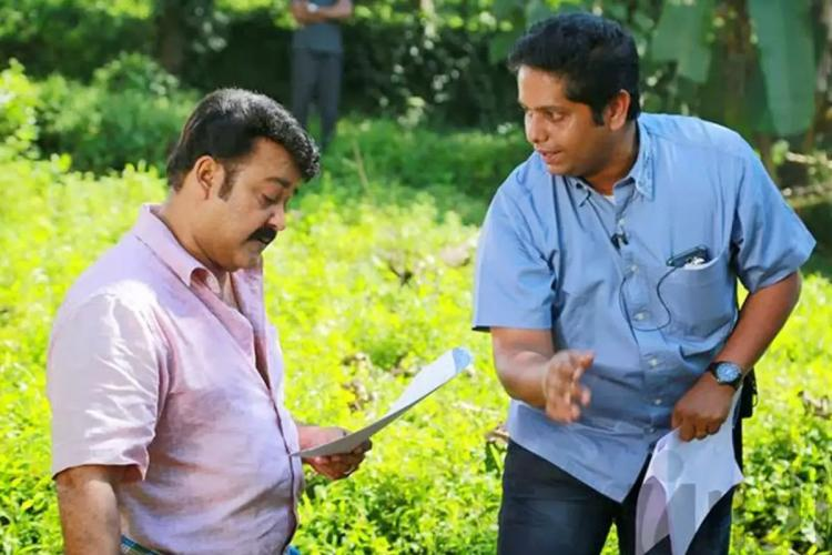 Mohanlal reads out from a paper as Jeethu talks to him both of them standing in a green field