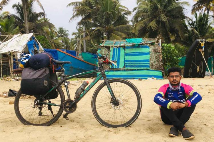 Jibin George along with his bicycle sitting on a beach