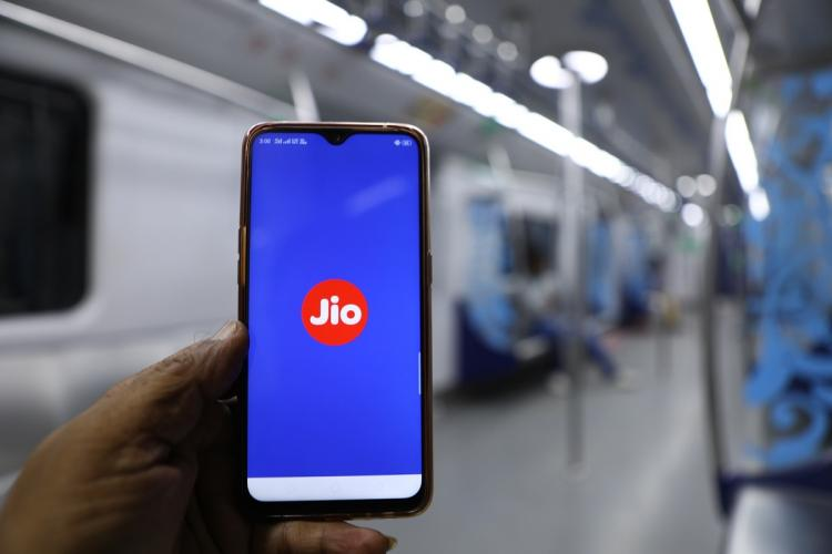 Person in a metro holding up a phone with Jio app open