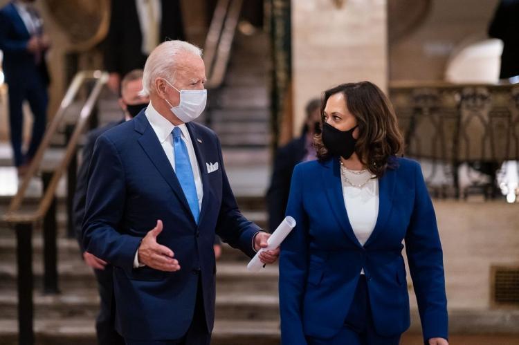 US President Joe Biden and Vice President Kamala Harris speaking while wearing masks