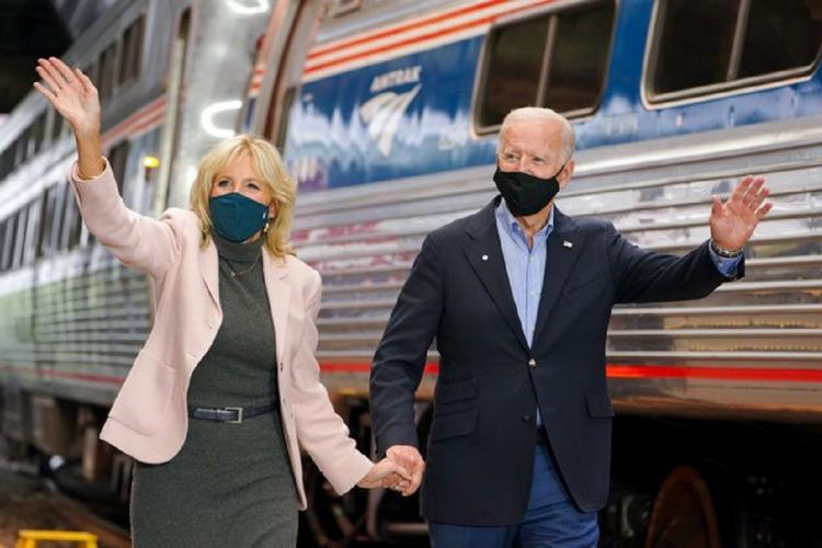 Jill and Joe Biden walk hand in hand wearing masks as their other hands are waving towards a public not seen in the photo