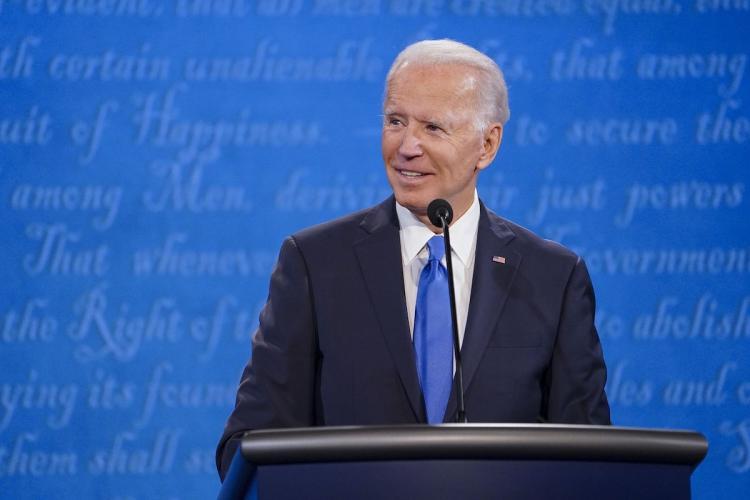 US President Joe Biden in a black suit and blue tie He is looking towards the left smiling