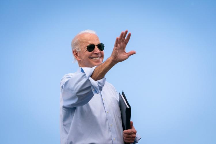 Joe Biden wears sunglasses and waves his right hand against a backdrop of blue