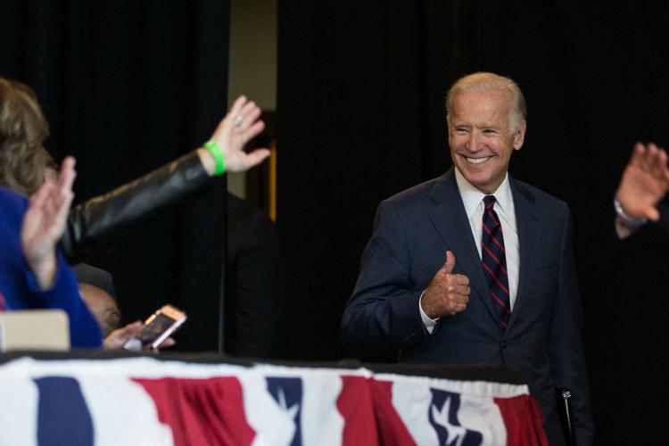 Joe Biden gives a thumbs up as someone waves at him