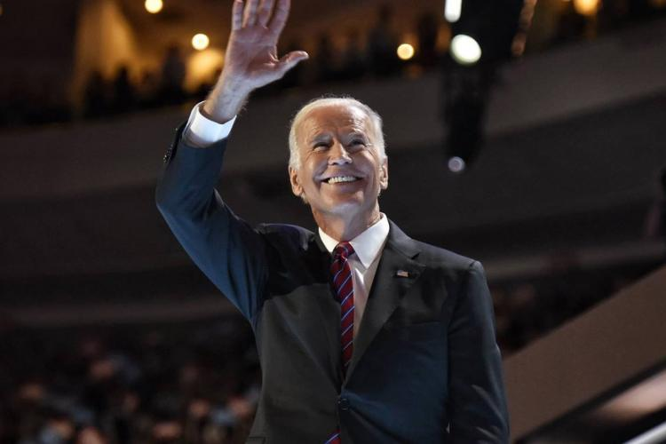 Democrats Presidential candidate Joe Biden wearing a back suit and red tie He is waving at a crowd and is smiling
