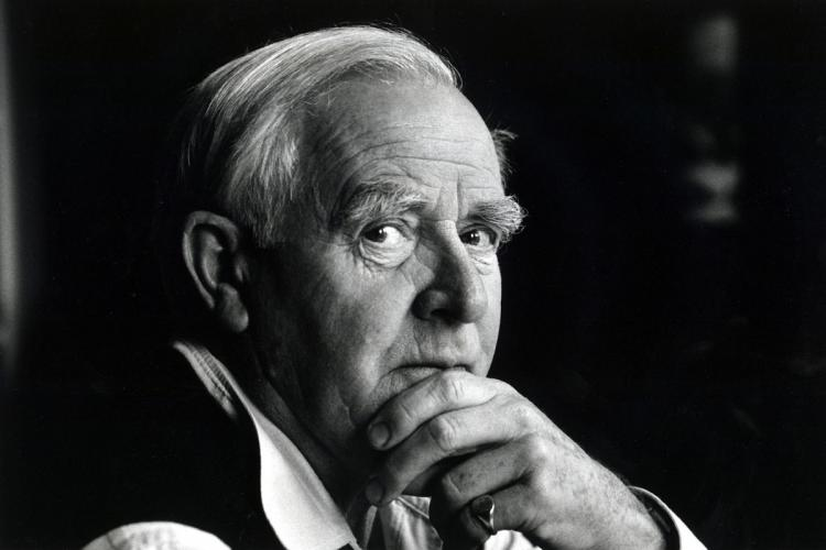 A black and white image of John le Carr He has his hand to his chin and looks up
