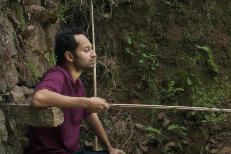 Fahadh wearing a dark purple t shirt sits sideways in front of a stone wall and has a fishing rod in his hand