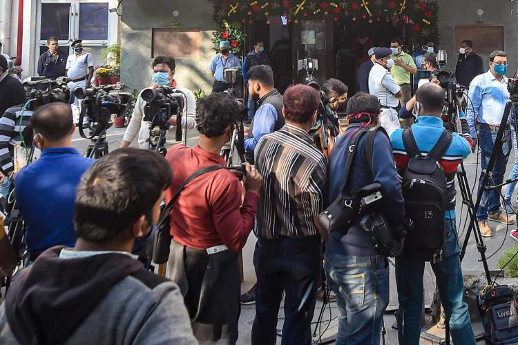 Reporters and camerapersons standing in a crowd