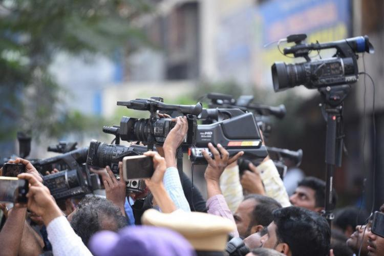 A group of journalists holding up cameras see from the side