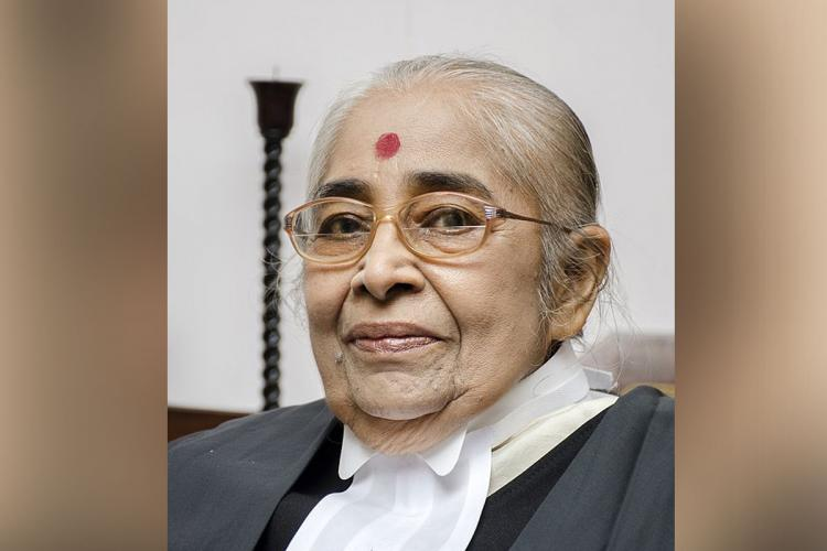 KK Usha in her judge's uniform with specs, grey hair tied behind her and a big red bindi on her face
