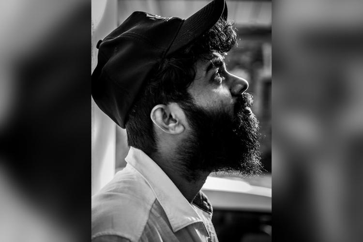 Black and white image of Justin Vargheses side profile wearing a cap a beard and looking up