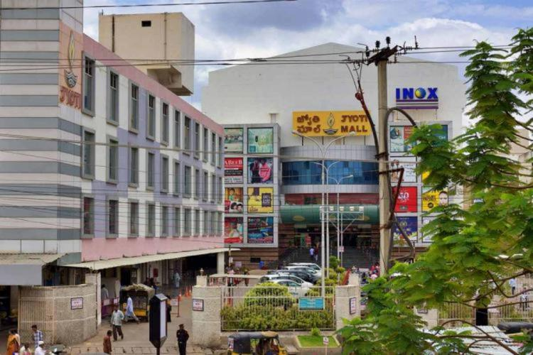Inox theatre and Jyothi mall in Kurnool seen from a distance with the facade of the building and the trees visible
