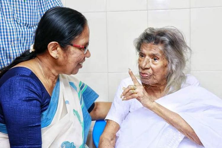 CPIM leader KK Shailaja in a white and blue saree speaking to Gouri Amma