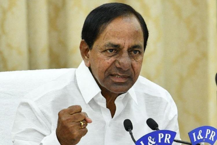 Telangana CM KCR in a white shit speaking into a mic with a clenched fist raised