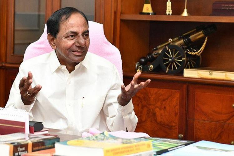 Telangana CM KCR dressed in white with hands outstretched and smiling looking to his left
