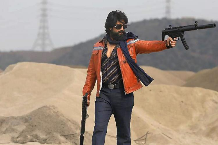 Yash can be seen wearing an orange jacket with two weapons in both the hands in sand mines