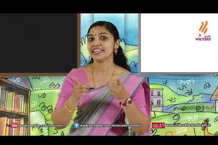 A teacher in a purple Sari teaches on a TV screen with hand gestures