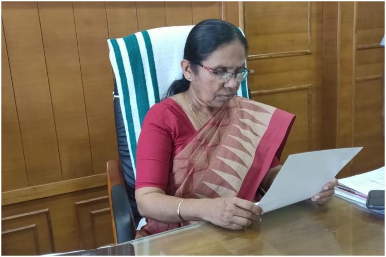 Kerala Health Minister KK Shailaja reading a note sitting at her office