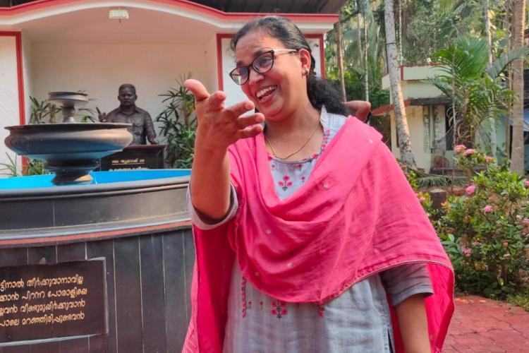 Kerala RMD leader K.K Rema against the background of statue of slain husband P.P Chandrashekhar