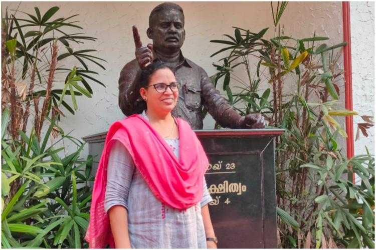 KK Rema Kerala Assembly poll candidate from Vadakara wearing a grey salwar and pink dupatta standing near the statue of her slain husband TP Chandrasekharan