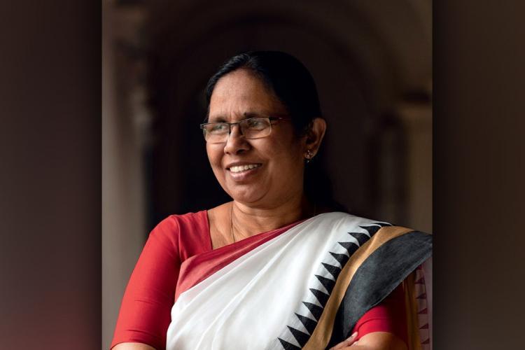 Shailaja smiles, wearing a white sari with black border and red blouse