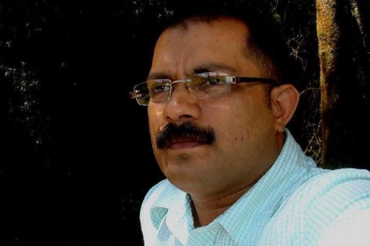 Shaji in a white shirt ans wearing his specs looks at the distance