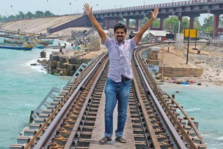 Basheer stands on a railway track running over the sea wearing a light violet shirt with both his arms raised up