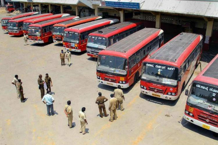 A picture from above of red color Karnataka RTC buses parked at a depot
