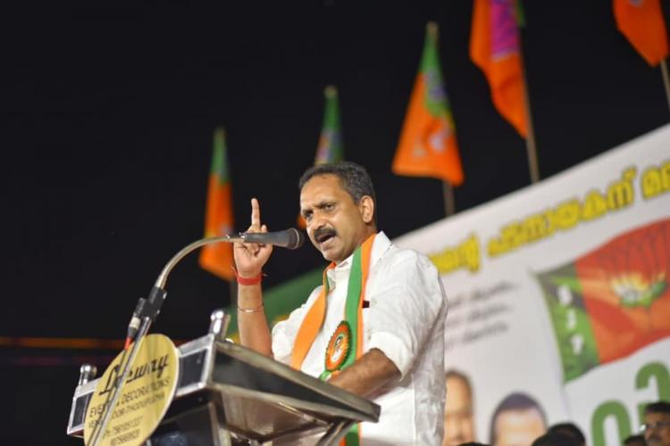 K Surendran state BJP president making a speech standing at a podium BJP party flags and a poster are seen in the backdrop