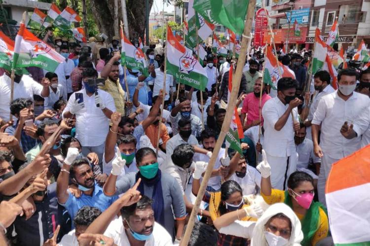 Scores of protesters - men and women - seen holding up Youth Congress flag and fists in the air raising slogans against Minister KT Jaleel Many are seen wearing masks