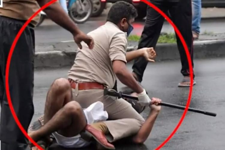 A police man can been seen pinning a man to the ground The man is seen in white mundu and black shirt The police man is wearing in a black face mask and hand gloves Both the police official and the man have held on the formers baton
