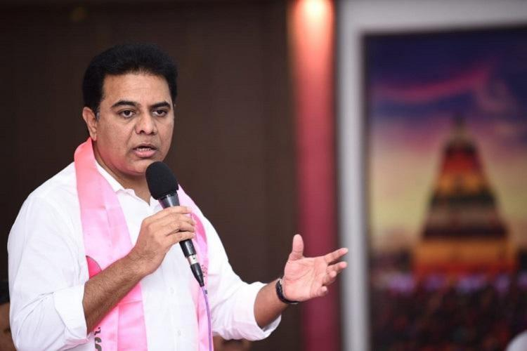 KTR in a white shirt and pink scarf speaking into a mic