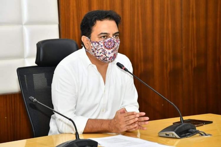 KTR seen wearing a cloth mask and white shirt while addressing a gathering in a mike in a chamber